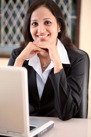 Relaxed young business woman at work photo