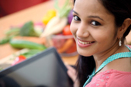 woman apron: Young Indian woman using a tablet computer in her kitchen Stock Photo