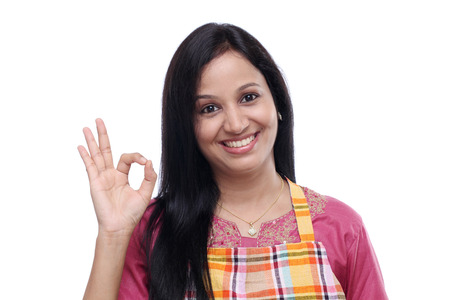 woman apron: Happy young Indian woman wearing kitchen apron and showing thumbs up