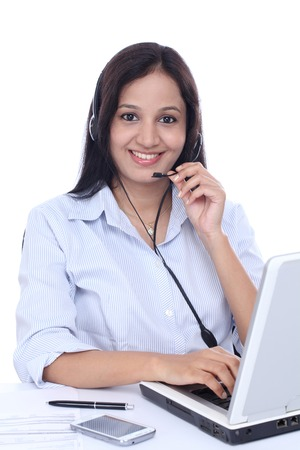 Smiling young Indian call centre woman with headset against white  photo