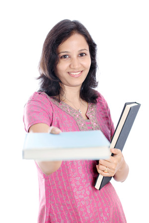 Smiling Indian female student holding books against  photo