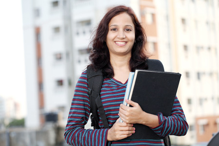 Smiling Indian female student holding books  photo