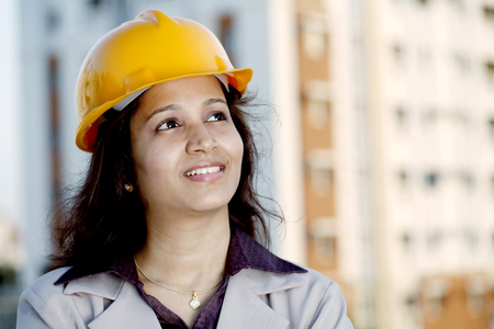 Young Indian female construction engineer looking up photo