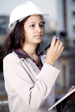 Young Indian female construction engineer with clipboard