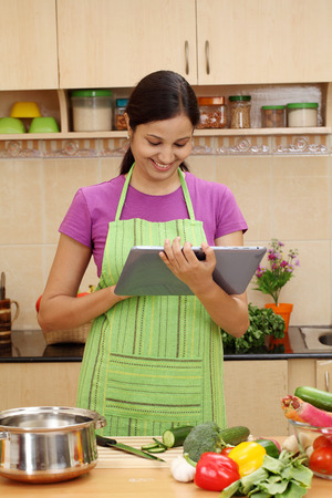 Young Indian woman using a tablet computer in her kitchen  Stock Photo