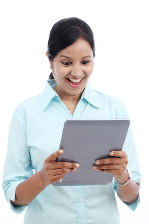 Excited young business woman looking at touch pad PC against white photo