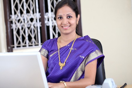 Smiling young traditional woman working at office photo