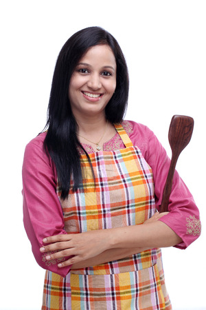 Young Indian woman holding kitchen utensil against white background photo