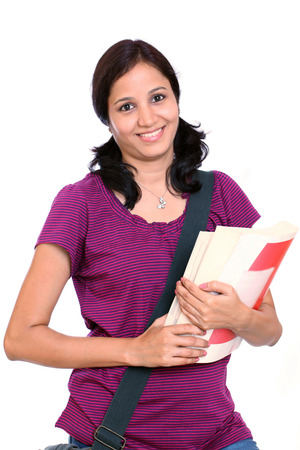 Young Indian female student holding books in her hand photo