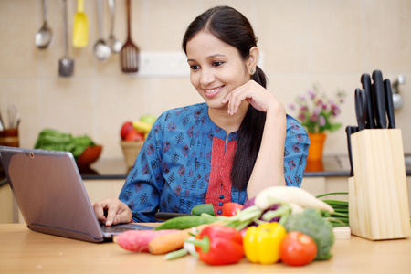 fille indienne: Jeune femme indienne en utilisant un ordinateur tablette dans sa cuisine Banque d'images
