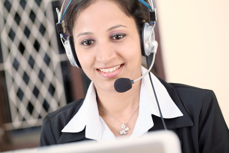 Close up of young indian business woman with headset