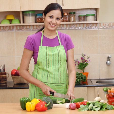 Smiling young Indian woman cutting vegetables Stock Photo