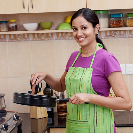 Young woman preparing a dish in her kitchen  Stock Photo