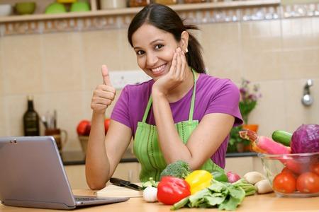 Lachende jonge vrouw die thumbs up gebaar Stockfoto