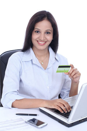 Happy young business woman doing online shopping against white Banco de Imagens