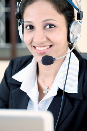 Close up of young indian business woman with headset photo