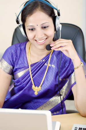 Happy young Indian businesswoman in traditional Indian dress with headset  photo