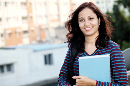 Cheerful young female college student at campus photo