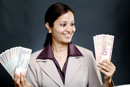 indian money: Happy young business woman holding Indian rupee notes Stock Photo