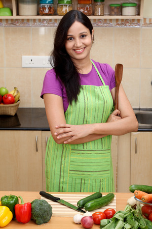 Smiling young Indian woman in her kitchen photo