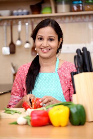 mujeres latinas: Mujer india joven que cocina en la cocina Foto de archivo