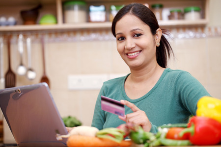 Smiling woman online shopping using computer and credit card in kitchen  photo