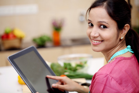 Young Indian woman using a tablet computer in her kitchen  photo