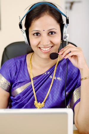 Young Indian woman in traditional Indian dress with headset  photo
