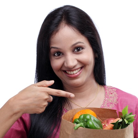 Young Indian girl holding grocery bag with full of fruits and vegetables photo