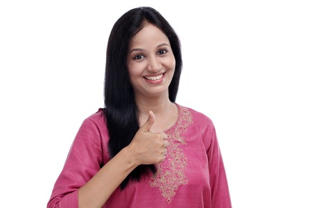Young Indian woman showing thumbs up gesture against white photo