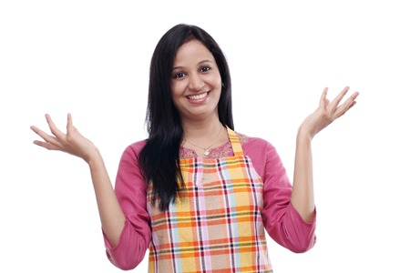 Excited young woman wearing kitchen apron against white background