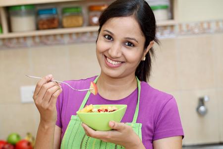 woman apron: Young woman eating fruit salad