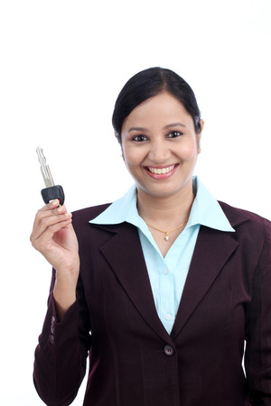 Happy young Indian business woman holding key against white background photo