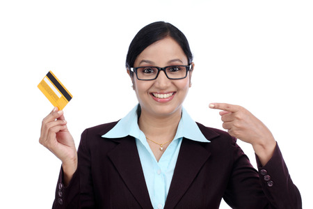 topicality: Happy young business woman holding credit card against white background