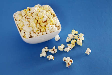 Bowl of delicious popcorn isolated on blue background photo