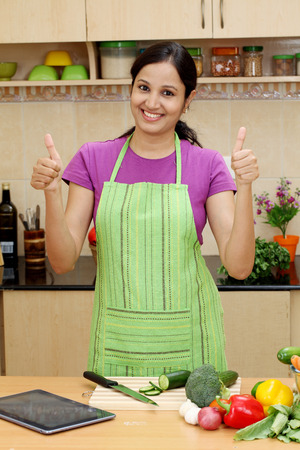 Happy young woman with kitchen apron and making thumbs up gesture  photo