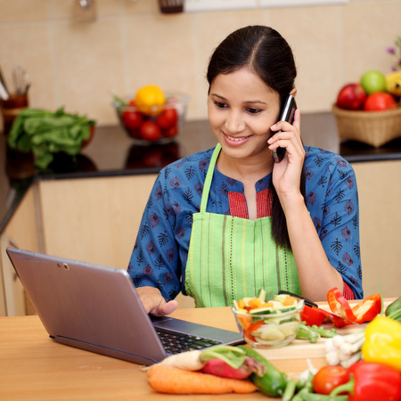 Happy woman working with tablet and talking on cellphone in kitchen