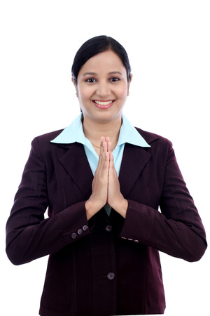 Smiling young business woman greeting Namasthe against white photo