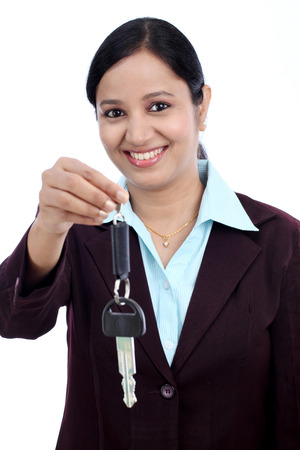 Happy young Indian business woman holding key against white background Stock Photo - 27743941