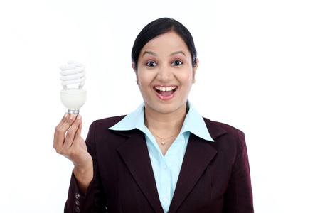 Young Indian business woman holding bulb against white background photo