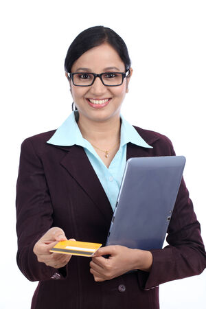 topicality: Smiling young business woman with table and credit card against white background