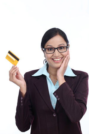 topicality: Surprised young business woman with credit card against white background Stock Photo