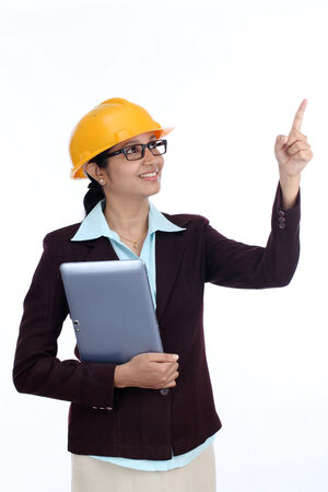Young Indian female engineer with tablet against white background photo