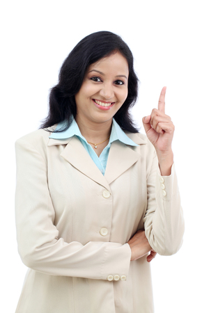 Confident business woman pointing up against white background photo