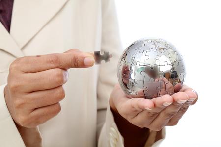 Business woman hand holding jigsaw puzzle globe photo