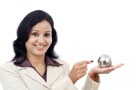 Young Indian business woman holding puzzle globe against white photo