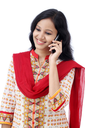Beautiful young woman talking on mobile phone against white background photo