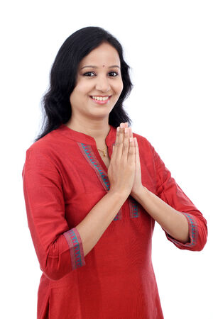 Smiling young woman greeting Namasthe against white background photo