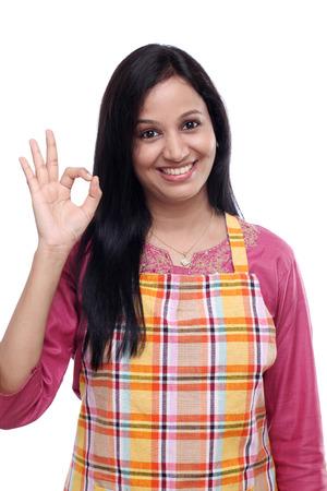 delantal: Mujer india joven feliz vistiendo delantal de cocina y mostrando los pulgares para arriba Foto de archivo