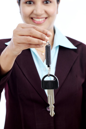 Happy young Indian business woman holding key against white background Stock Photo - 27755557